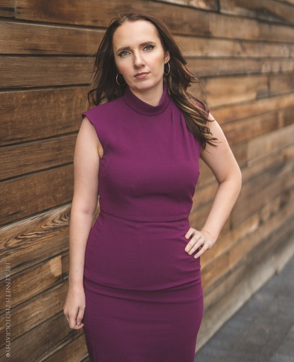 MJ Vogel posing outdoors, wearing a lovely plum-colored dress