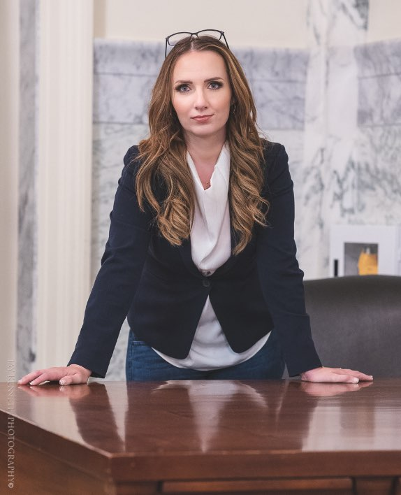 MJ Vogel leaning on a table, looking at the camera
