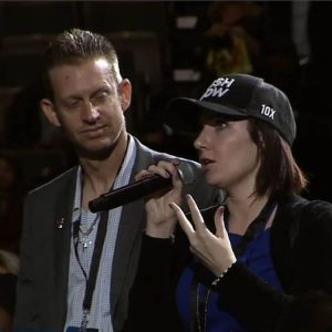 Woman in audience using microphone to as question, man standing next to her